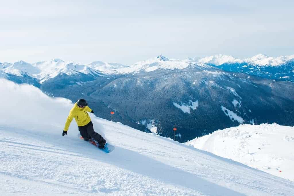 Snowboarding on a beautiful sunny day with Black Tusk in the background, Skiing fresh lines on Whistler Mountain, Tourism Whistler / Mike Crane